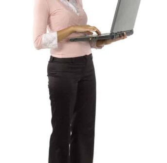 A woman standing and holding an open laptop.