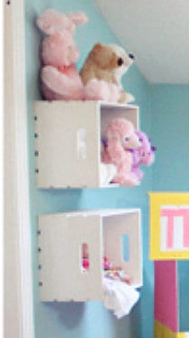 White cubes attached to the wall with toys in them.