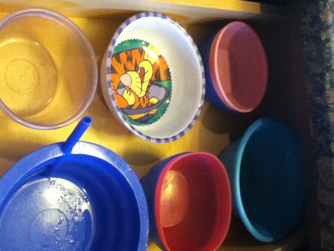 A close up of organized plastic bowls in a drawer.