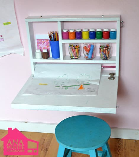 A child\'s homework desk with shelves filled with organized supplies and a blue stool under it.