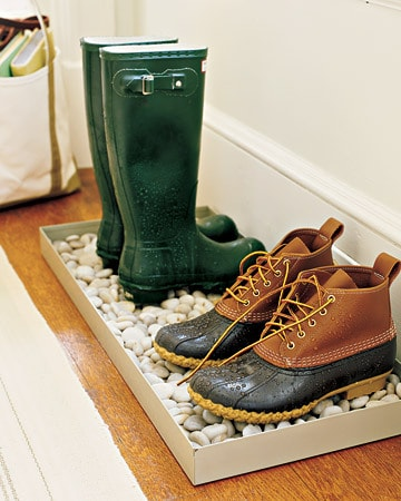 Two pair of boots sitting on a tray of stones.