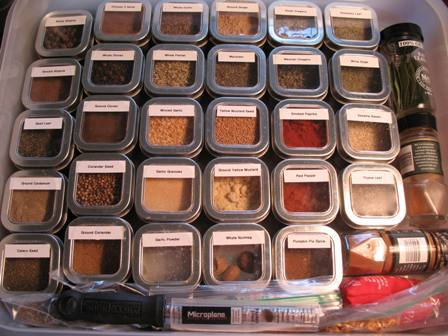 A plastic container with a variety of spices in individual plastic cups with lids.