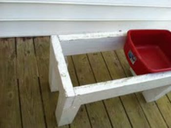 A wooden water table with a red plastic container in it.