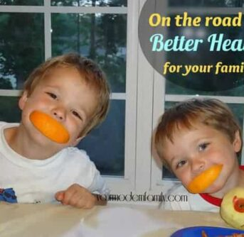 Two little boys sitting at the table with orange peels in their mouths with text above them.