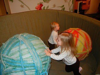 Two kids rolling huge balls of yarn around.