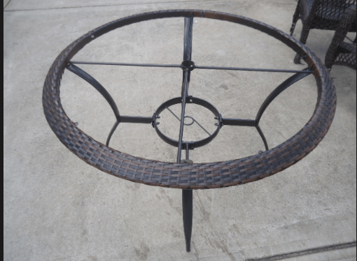 A close up of a round  table with the glass top removed.