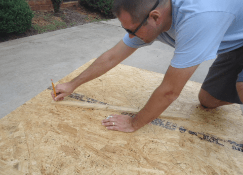 A man drawing a line with his pencil on a piece of plywood.