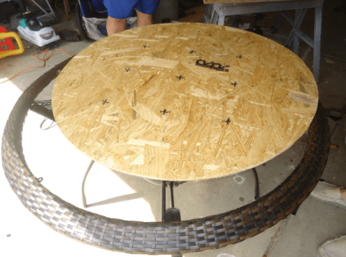 A piece of plywood cut into a circle sitting on top of a round table.