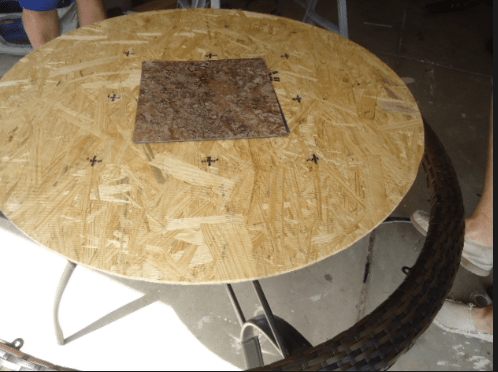 A round piece of plywood with a square piece of tile on top of it.