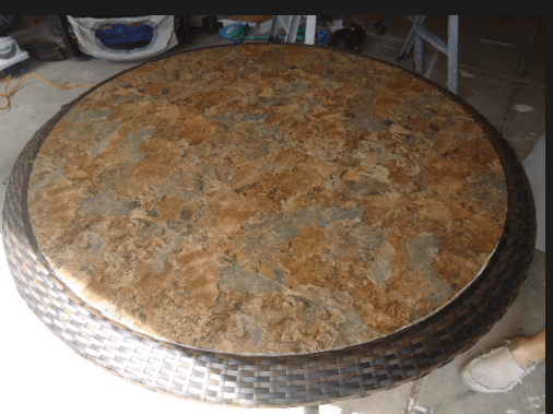 A round table with a round top made out of tiles.
