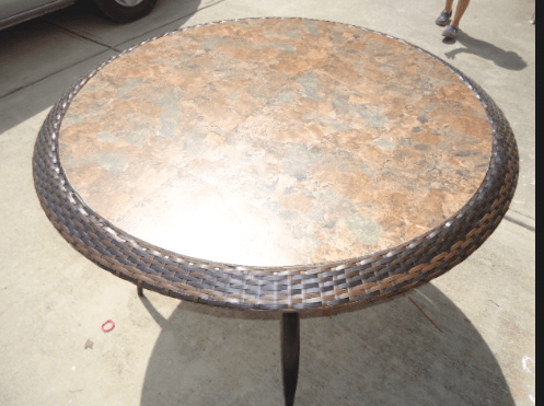 A round table with a tile top that replaced a glass top.