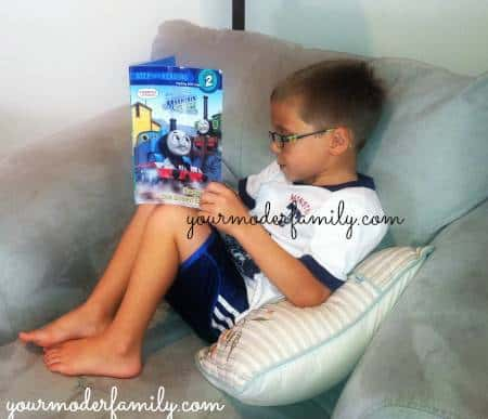 A little boy reading a Thomas the Tank book on the couch.