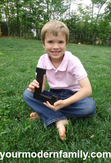 """A little boy that is sitting in the grass holding a wooden letter \""""L\""""."""