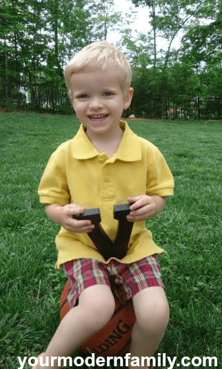 """A little boy that is kneeling in the grass holding a wooden letter \""""V\""""."""