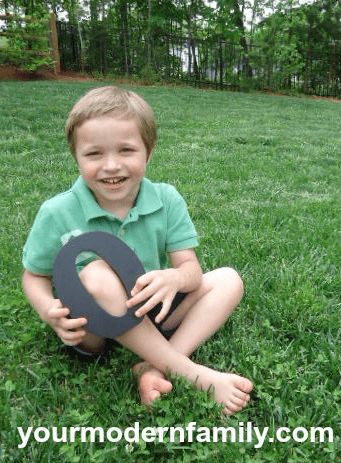 """A little boy sitting in the grass holding a wooden letter \""""O\""""."""