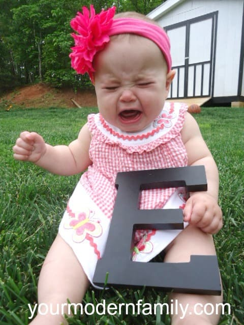 """A little girl that is sitting in the grass holding a wooden letter \""""E\"""" while she crys."""