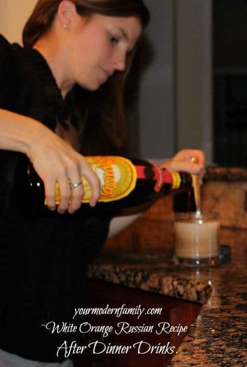 A woman pouring liquor into a glass.