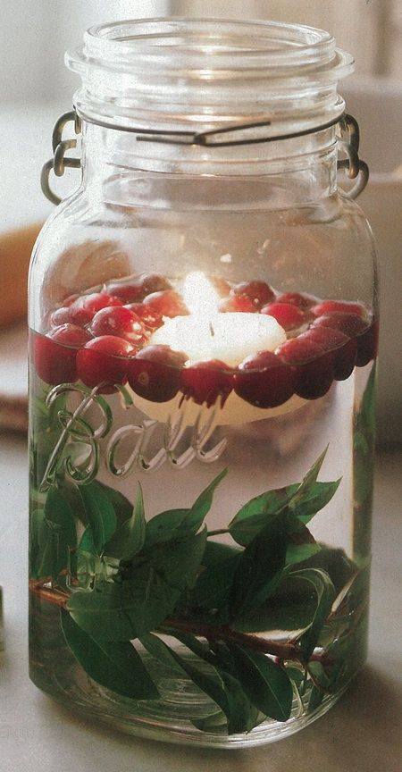 A Christmas candle in a mason jar with water and floating cranberries.