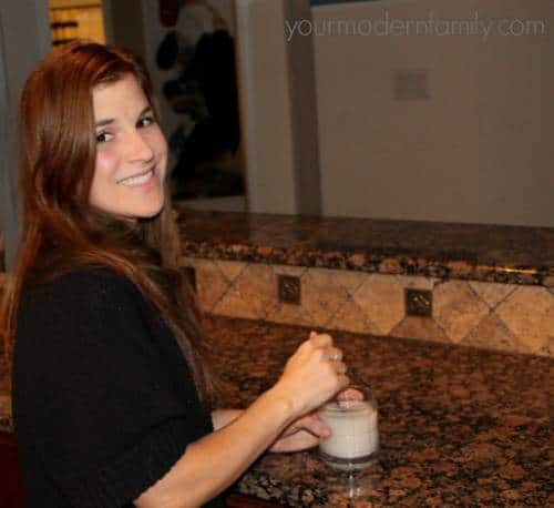A woman standing near a kitchen counter with a  White Russian drink.