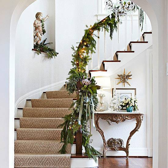A spiral staircase decorated with Christmas garland.