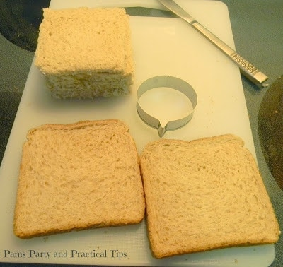 Slices of bread on a cutting board with a knife and circle cookie cutter beside them.