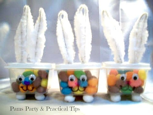 Plastic cups with candy in them with bunny ears as decorations.