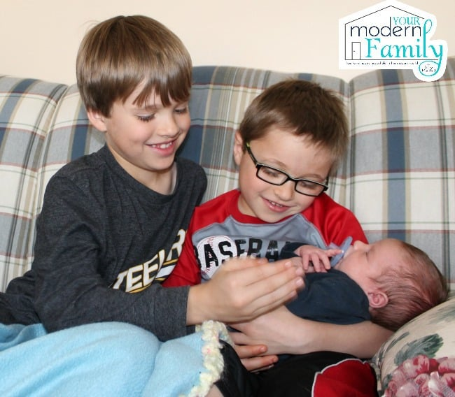 Two boys sitting on a couch holding a little baby.