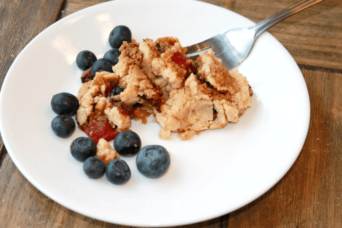A baked scoop of Dump Cake on a white plate with blueberries around it.