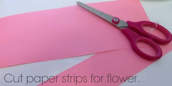 A close up of scissors and pink construction paper with text below them.