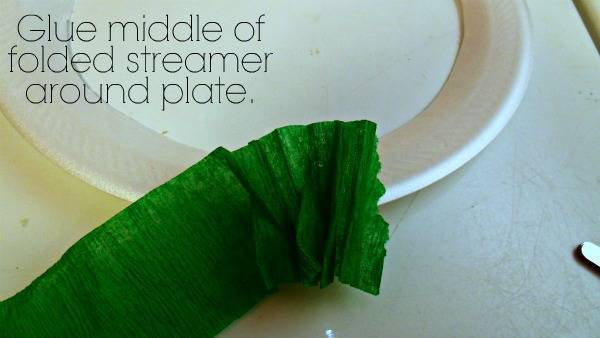 A close up of a green crepe paper and a white paper plate with text above it.