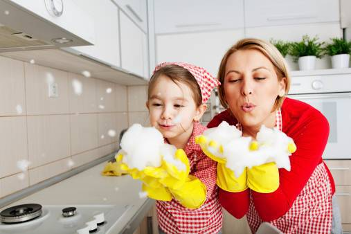 A little girl and a woman wearing yellow cleaning gloves and blowing bubbles off of them.