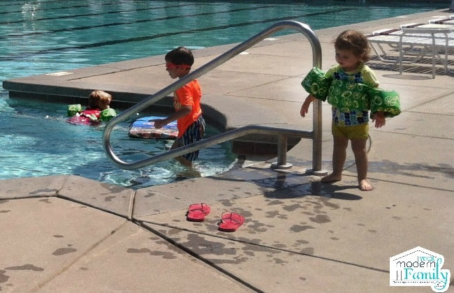 A little girl standing near the swimming pool stairs wearing a puddle jumper for safety while older children play in the pool.