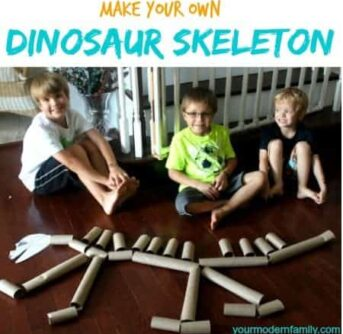A group of kids posing for the camera in front of a dinosaur made of paper towel rolls.
