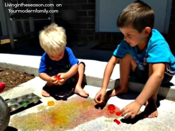 Two little boys sitting on a porch playing with melting colored ice cubes.