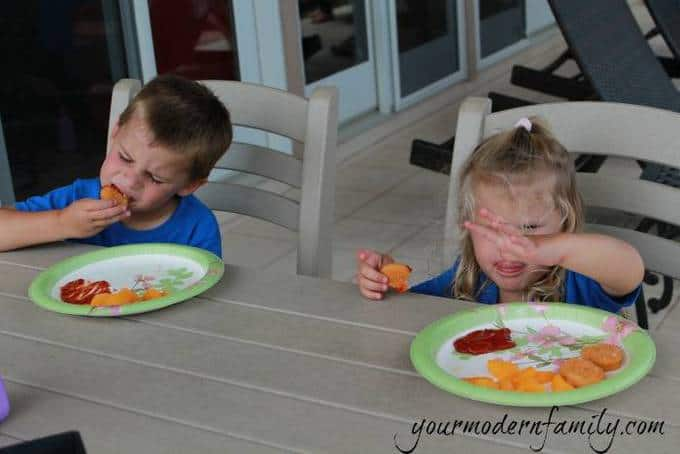 A little boy and girl sitting at a table eating food.