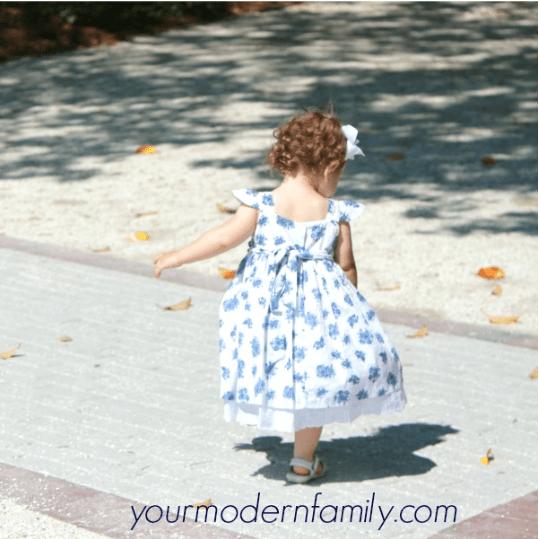 A little girl walking on a driveway.