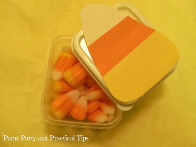 A plastic container with candy corn in it and a candy corn decoration on top.