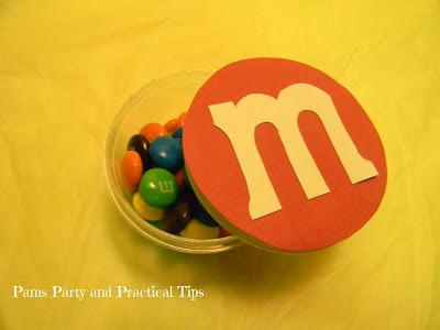 A plastic container of m&ms and an a M&M logo on top.