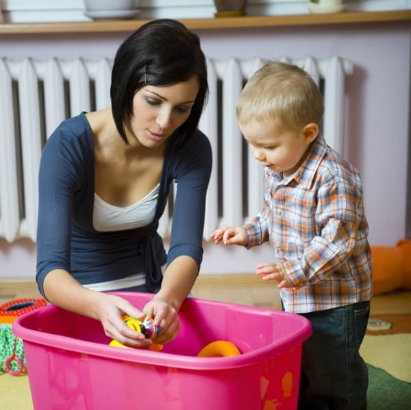 A woman and a child looking at toys in a laundry basket.