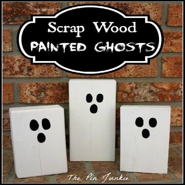 Wood scraps painted white to look like ghosts with text above them.