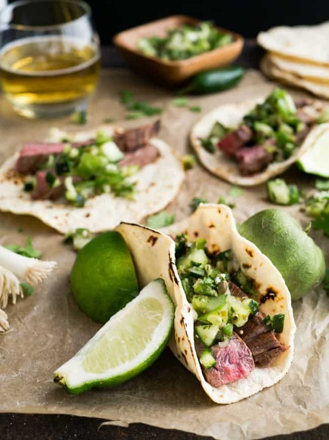 A table filled with soft taco shells filled with a variety of meats and vegetables.