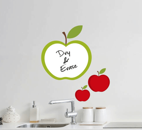 A white counter with a sink and apple dry and erase decals behind it.