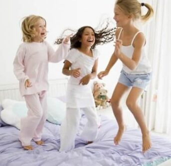 A group of kids jumping on a bed.