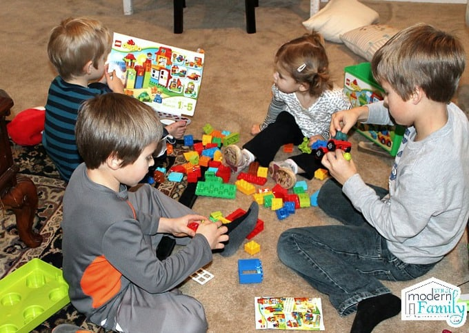 Four children sitting on the floor playing with Legos.
