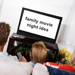 A view of a family sitting on the couch watching a movie together.