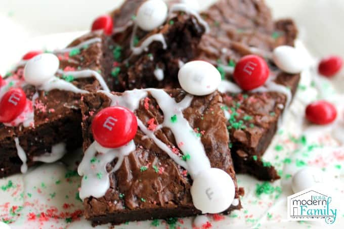 A close up of brownies with M&Ms and white chocolate icing.