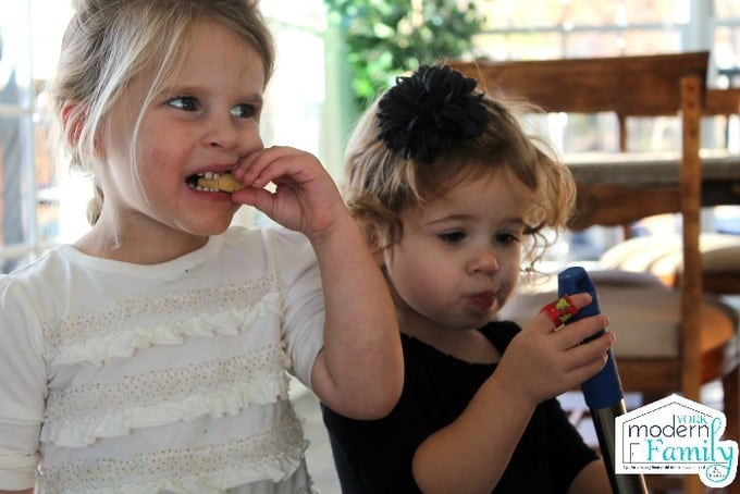 Two little girls eating M&M cookies.
