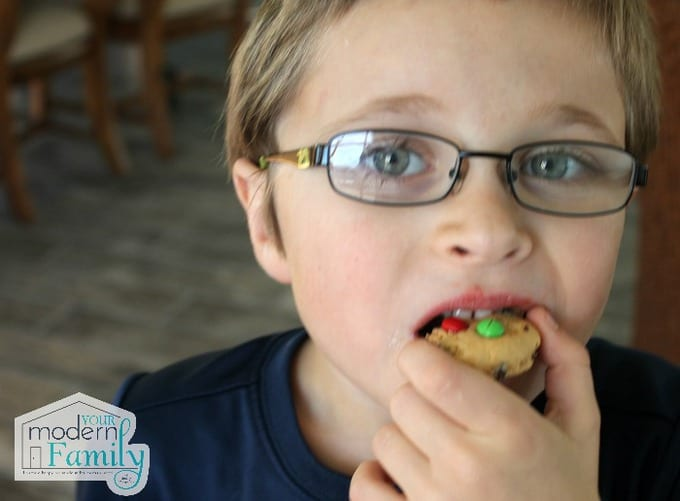 A young boy eating M&M cookies.