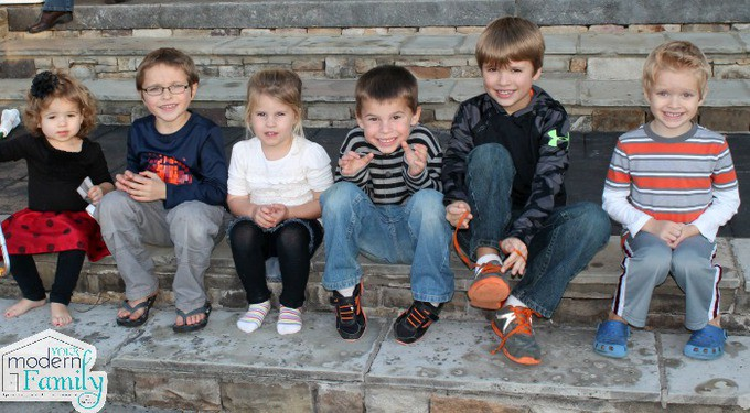 A group of young children sitting on a stone steps.