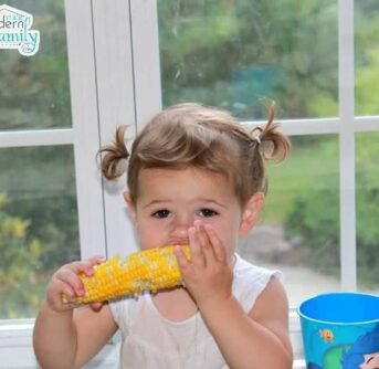 A young girl eating corn on the cob.